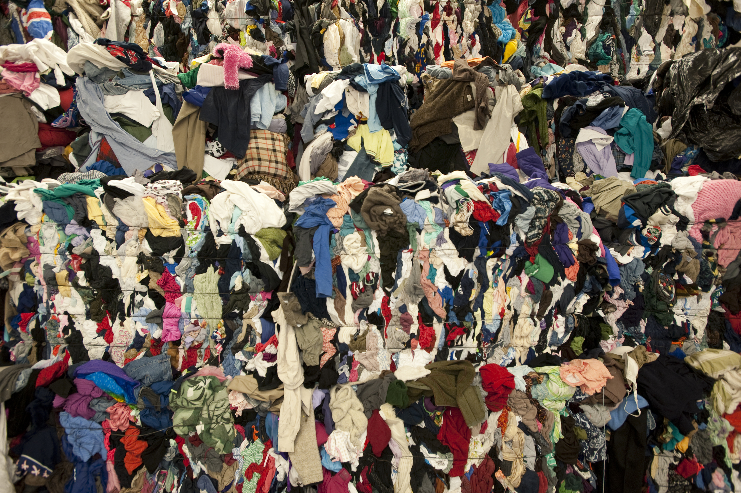 Bundles of clothing waste await recycling. Many discarded clothes end up outside the recycling system, clogging the world's landfills with an estimated 70 lbs per capita of garment waste in the US alone (photo: GreenGlamour )