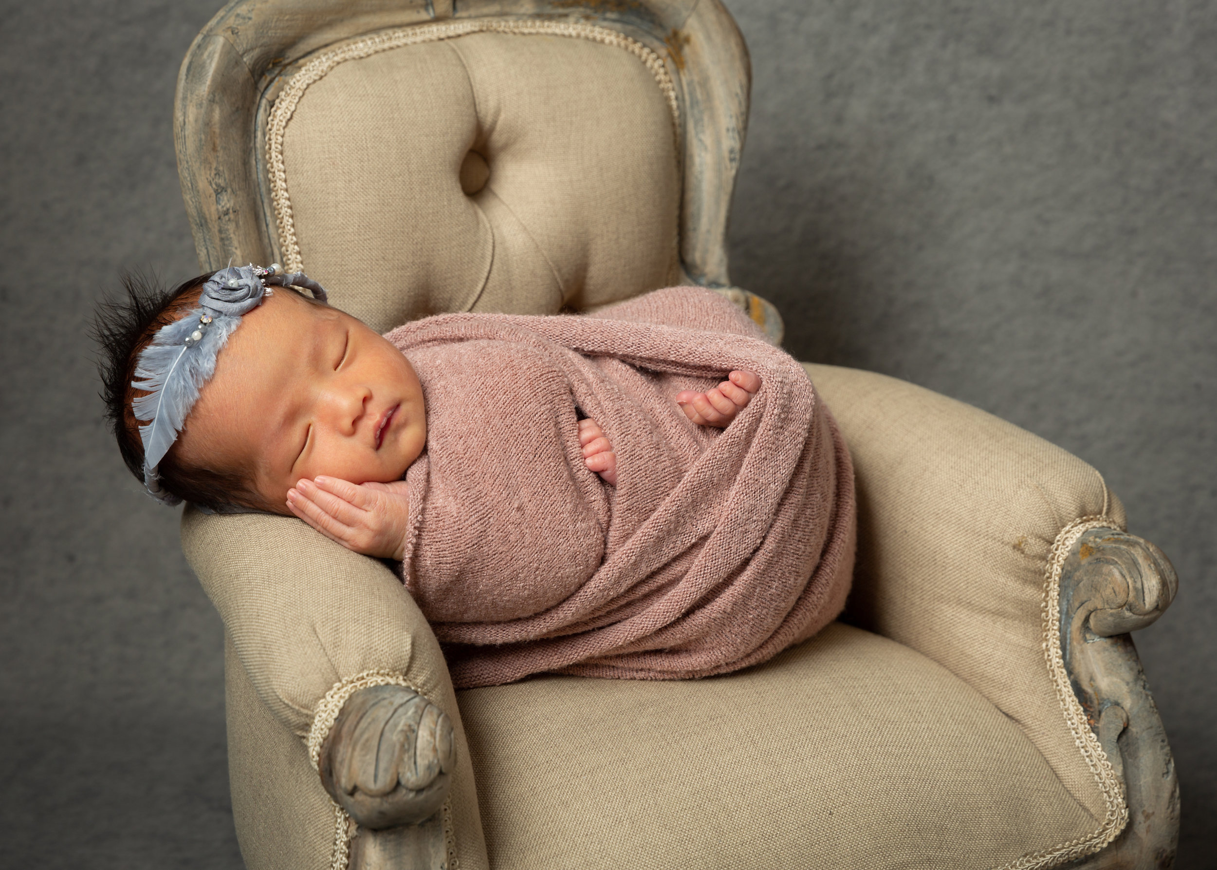 newborn-baby-wrapped-in-armchair