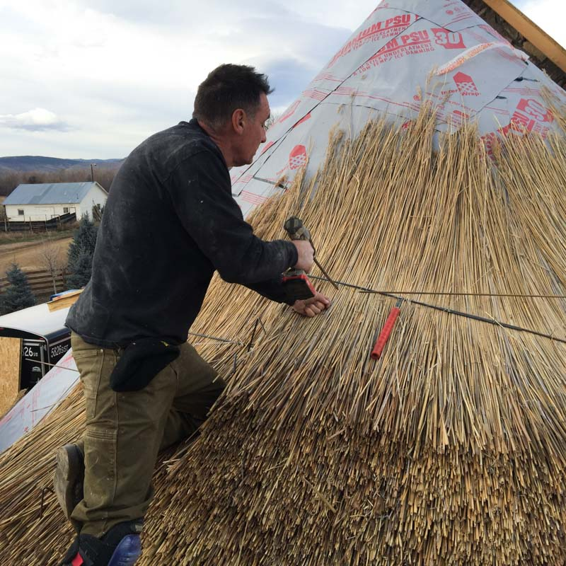 Securing the thatch down... each successive bundle will conceal the wire.