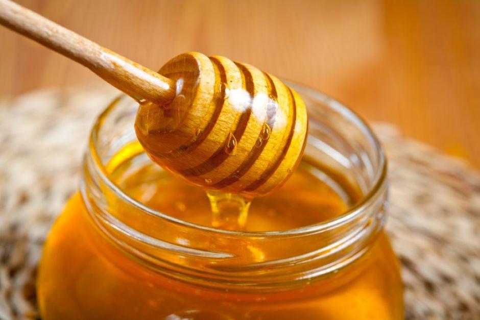 Spoonful of honey in a honey jar
