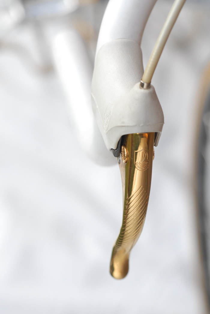 White brake hoods on Campagnolo Delta gold plated brake levers.