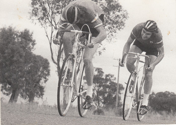 Armidale club racing about 1977. Single speed road bikes, we'd adapt as fixed wheel for training or put some derailleurs back on whenever needed or just race as single speed in club races. Chris Pratt attacks from behind, myself head down.