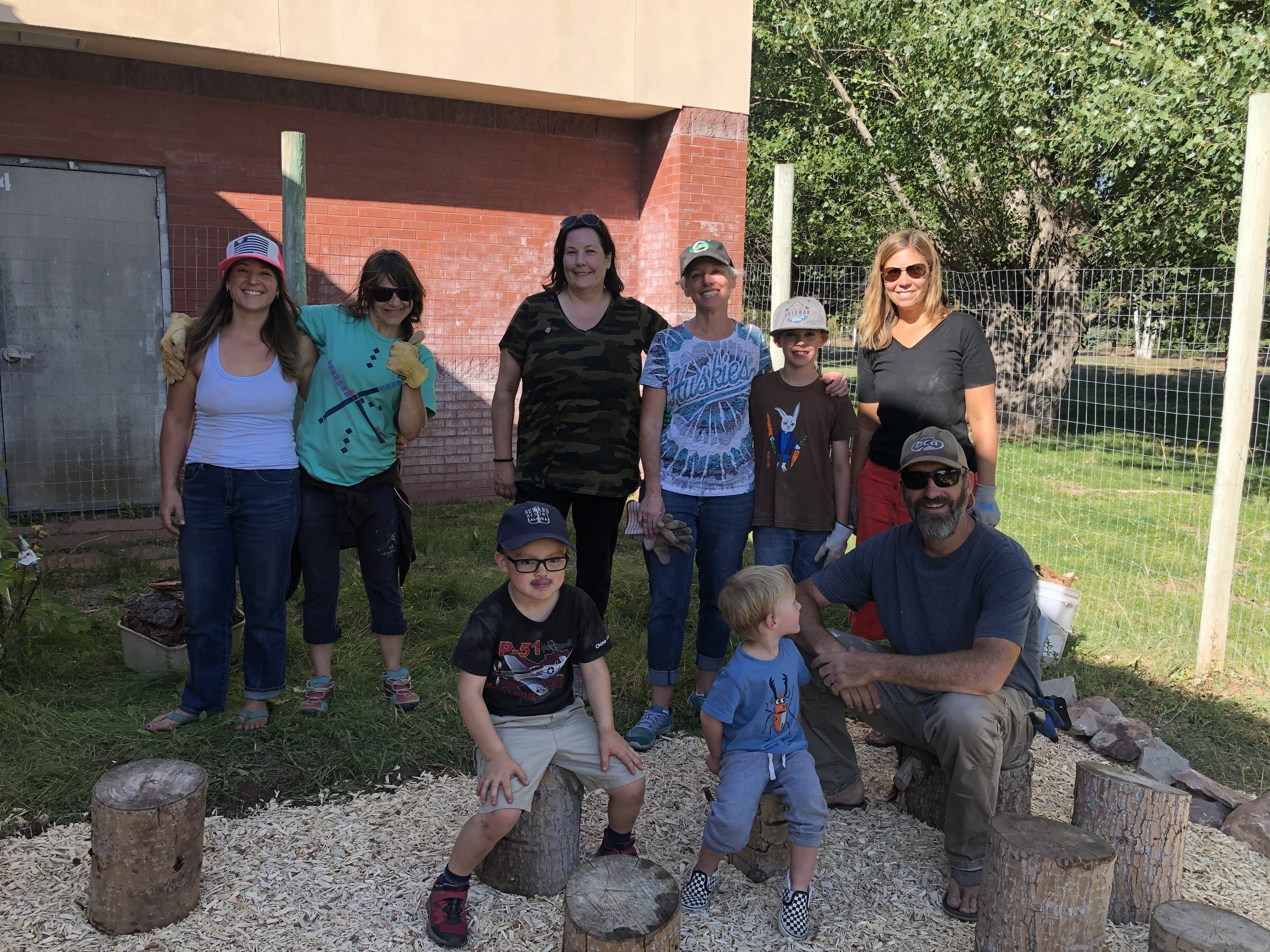 Our parent volunteers and kiddos pause to document our efforts cleaning up the Outdoor Classroom! Mulch, decorations, white board renovation, and beautiful stumps were added to enhance our students' outdoor learning experiences! Thanks all! (though not all who helped are pictured above)