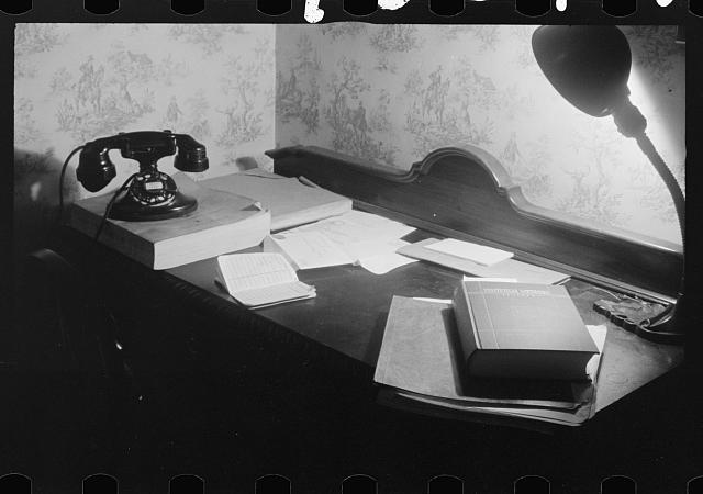 Washington, D.C. A government clerk's room, showing a desk with books, telephone and directory, and a desk lamp on it (1939) Library of Congress, Prints & Photographs Division [reproduction number LC-USZ62-131601]