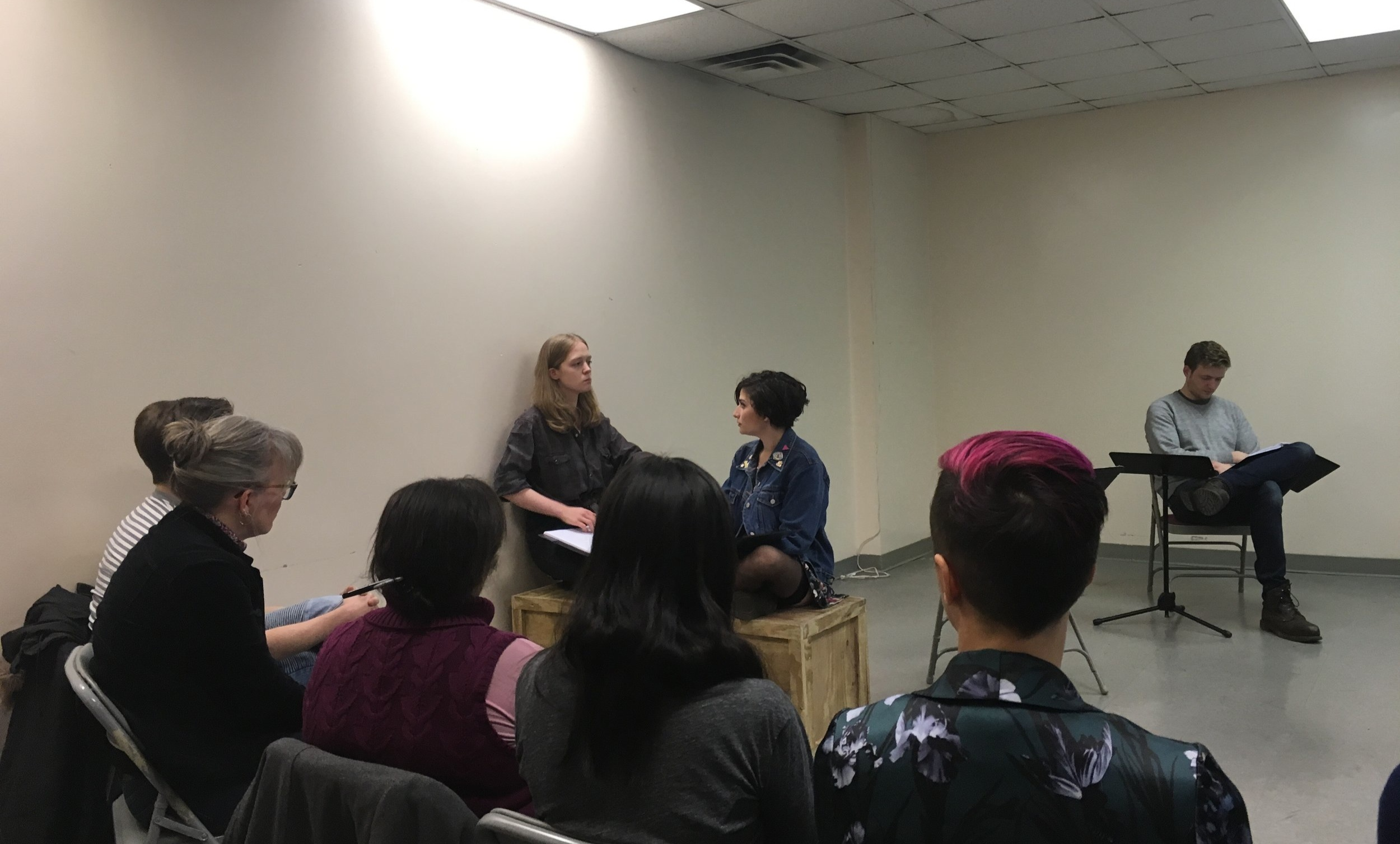 Ida and Alexis (Jackie Abbott) debate; the audience looks on. From the Trans Lab reading of  Boxcar  by Else C. Went (December 2018).