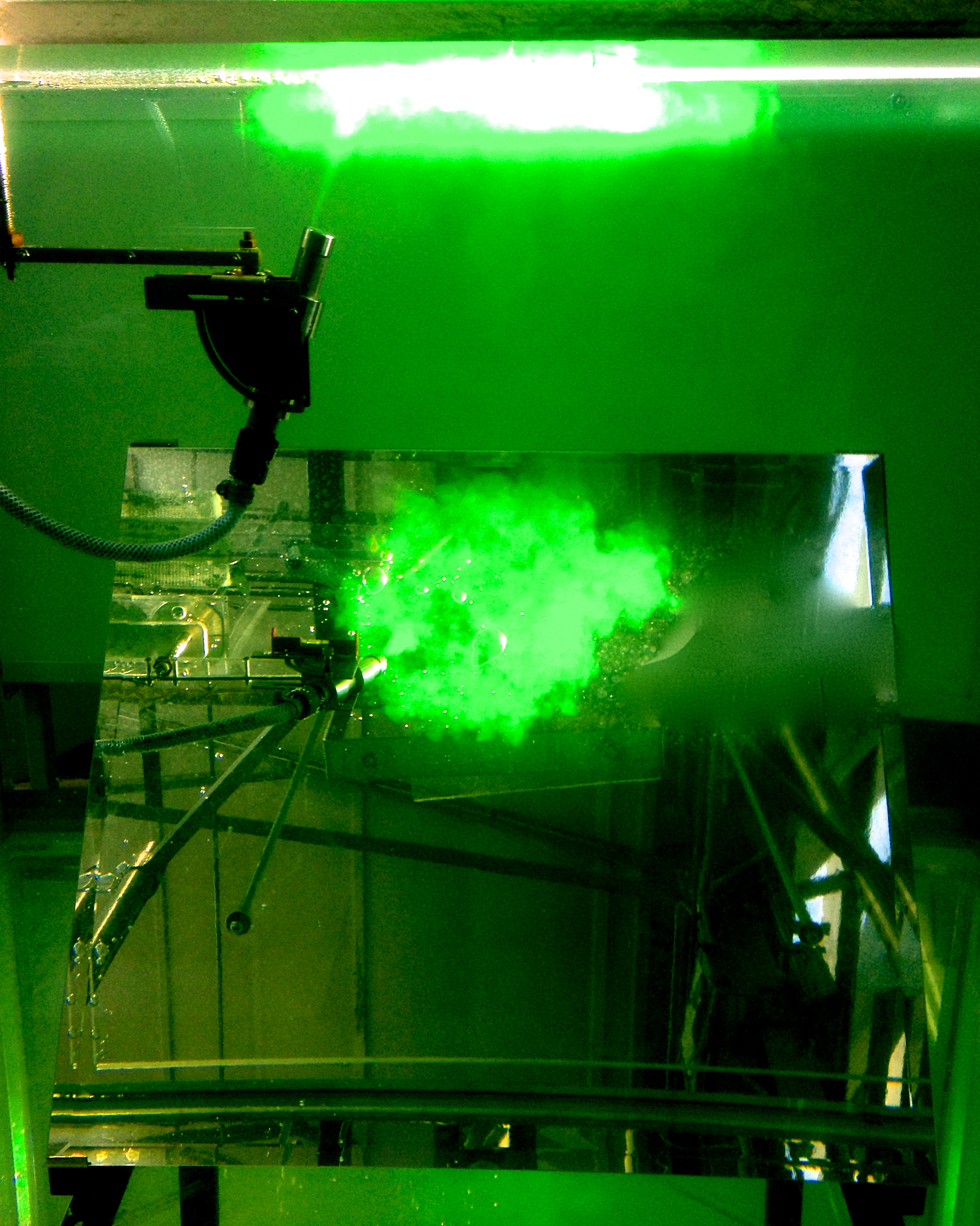 Photo of a 'salt bath' experiment, showing a jet of dyed saline hitting a surface, modelling a fan heater directed downwards towards the floor. Planar Light-Induced Fluorescence (PLIF) using a light sheet and fluorescein dye has been used to visualise the flow.