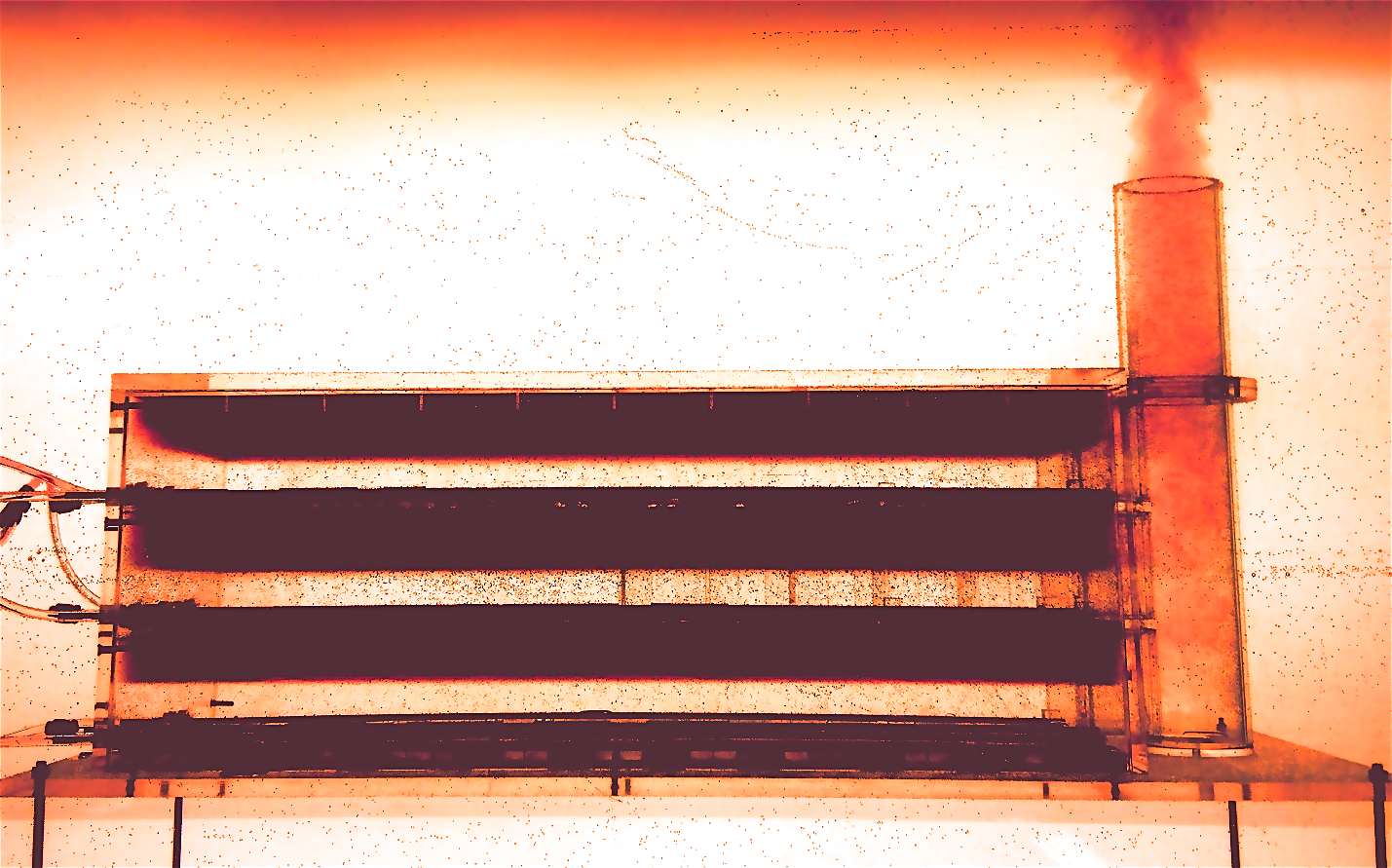 1:50 scale model of a naturally ventilated three-storey building with an exhaust stack. Saline, dyed red, is supplied to the storeys to model heat generated by people and equipment. The buoyant air rises upwards and leaves the building through the stack, causing fresh air to be drawn into the storeys through floor-level ventilation openings. Note that this photo is upside-down!