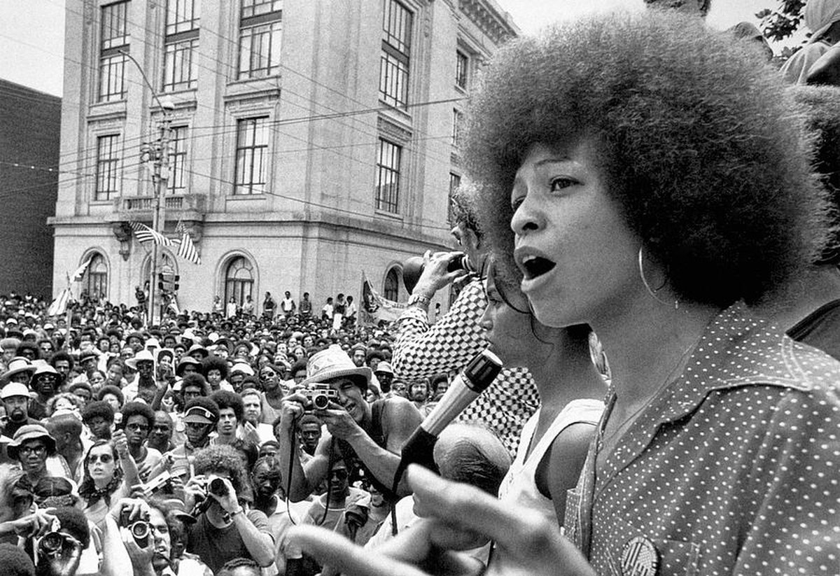 Black and white image of Angela Davis, who stands on the right hand side in front of a crowd.