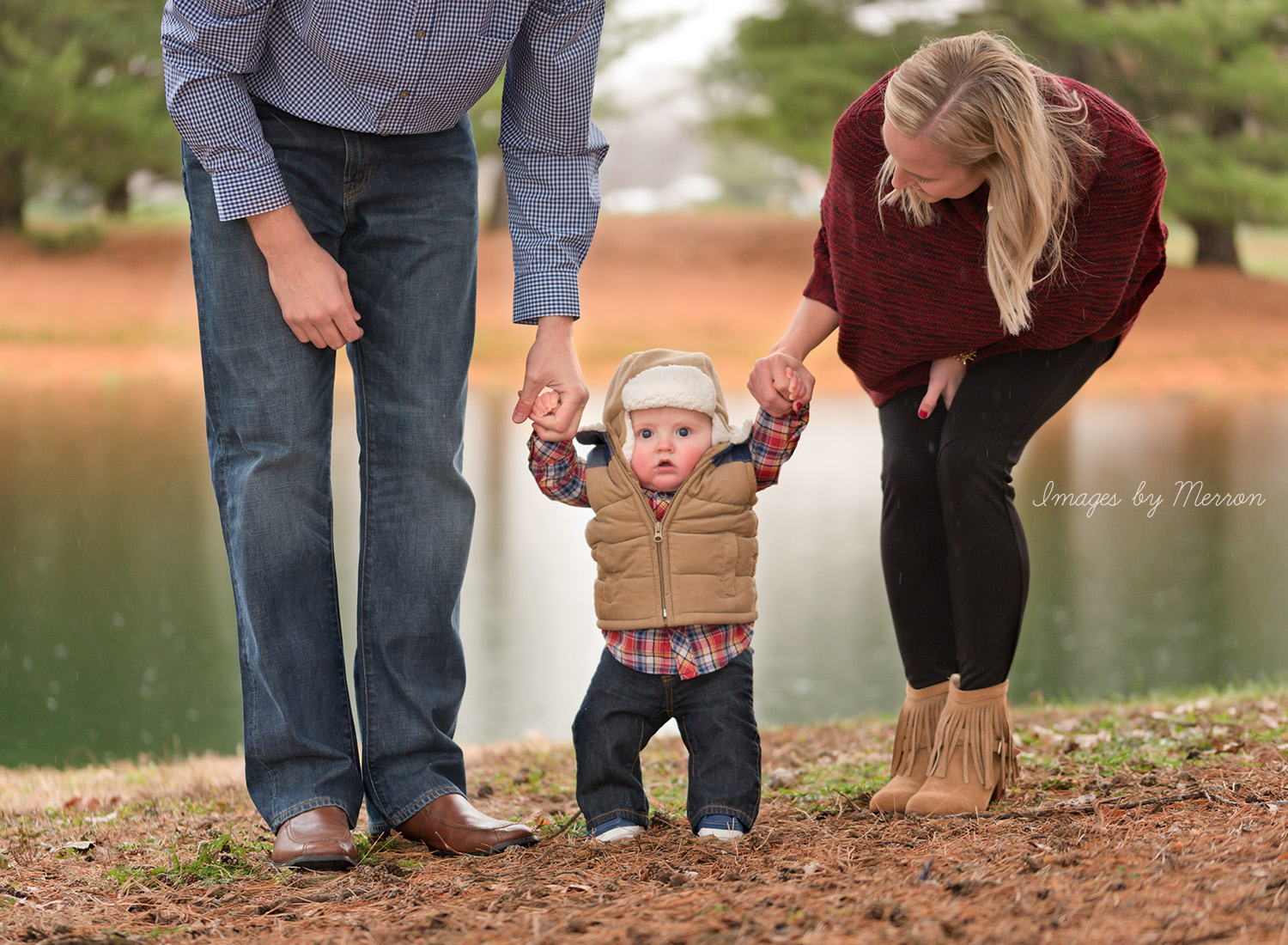 Mom & Dad helping baby stand on cold, drizzly day near pond