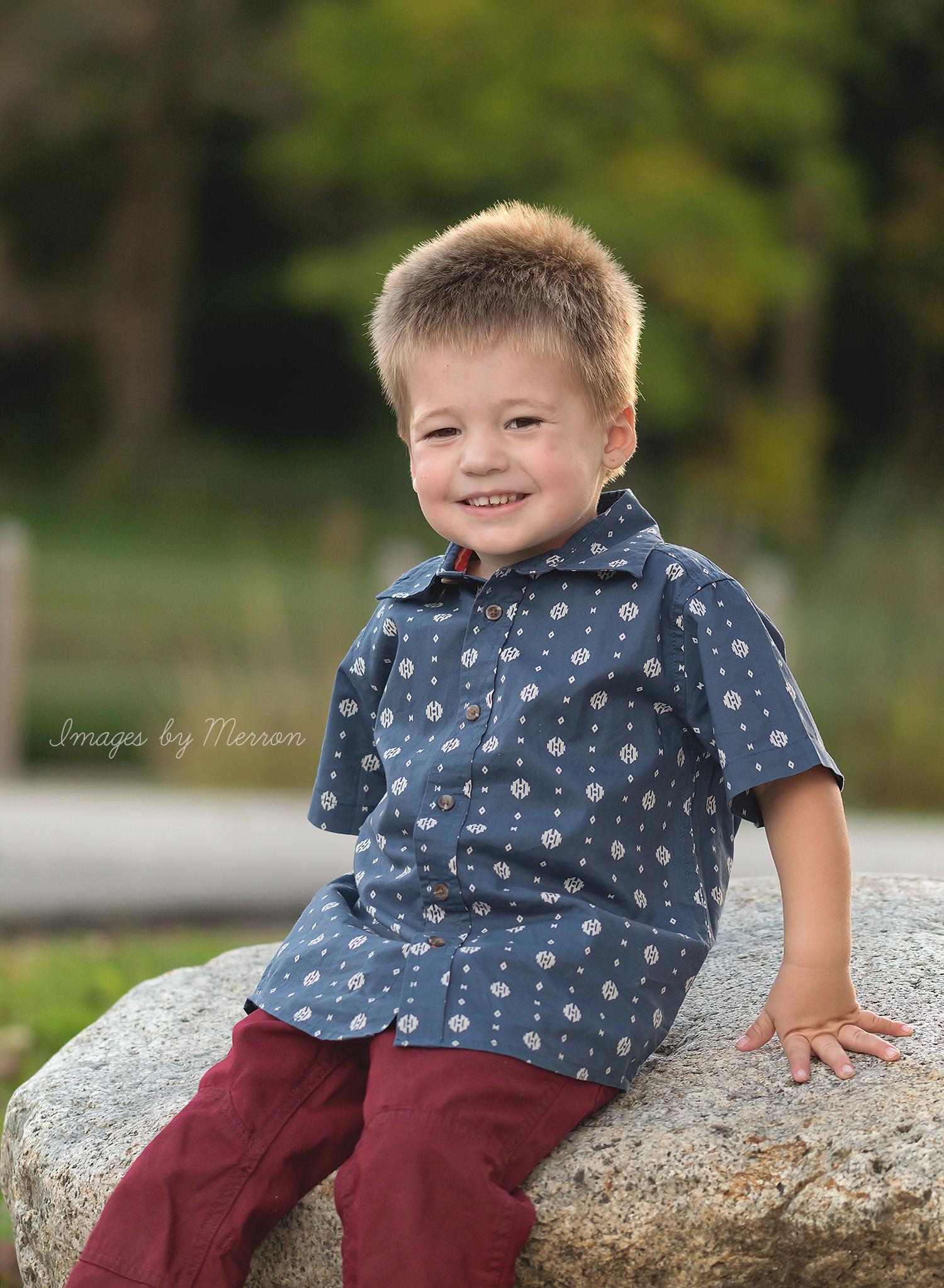 Little boy sitting on rock at Jester Park in Iowa
