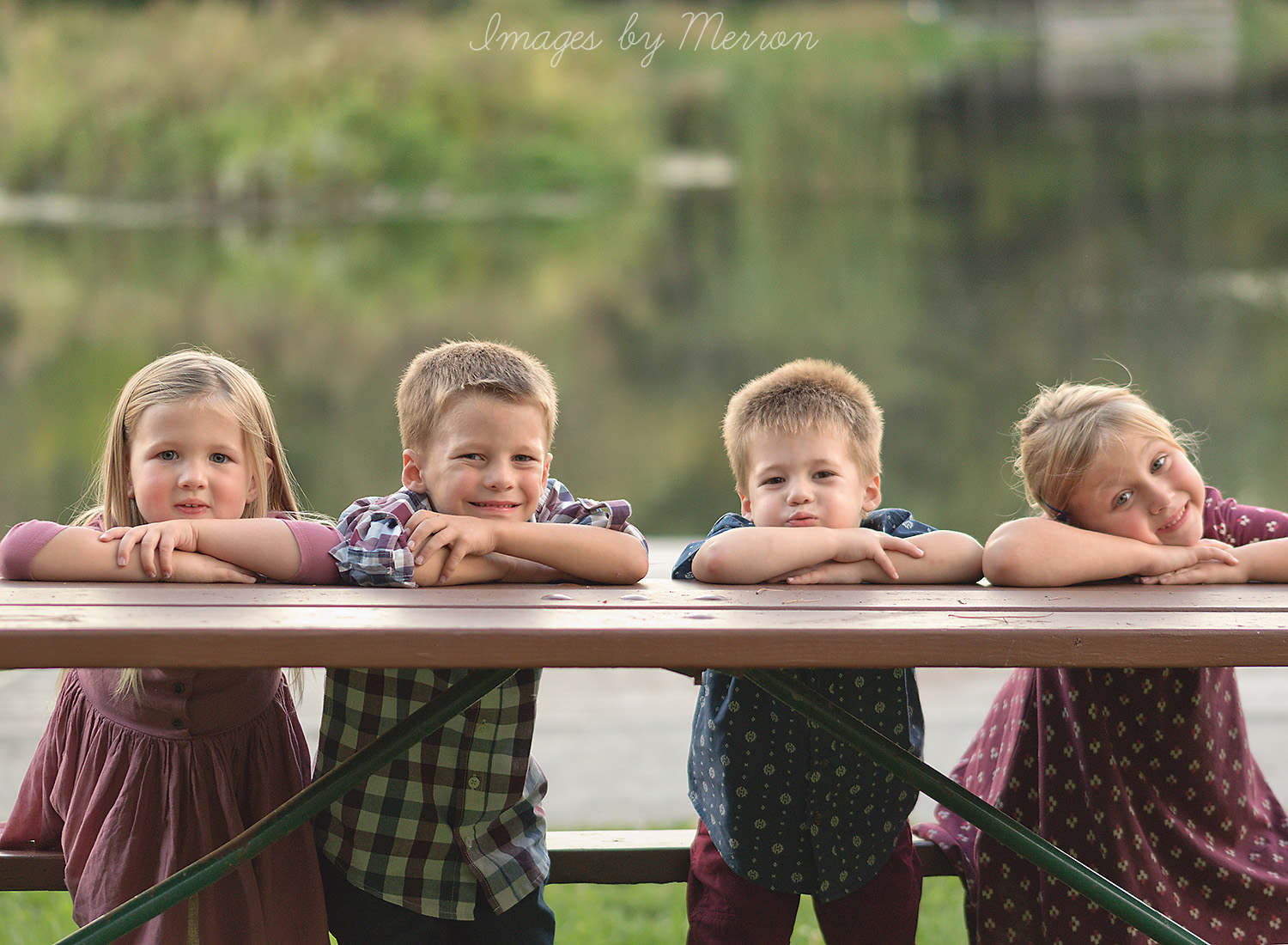 Four young cousins resting arms on picnic table, posing for photo session