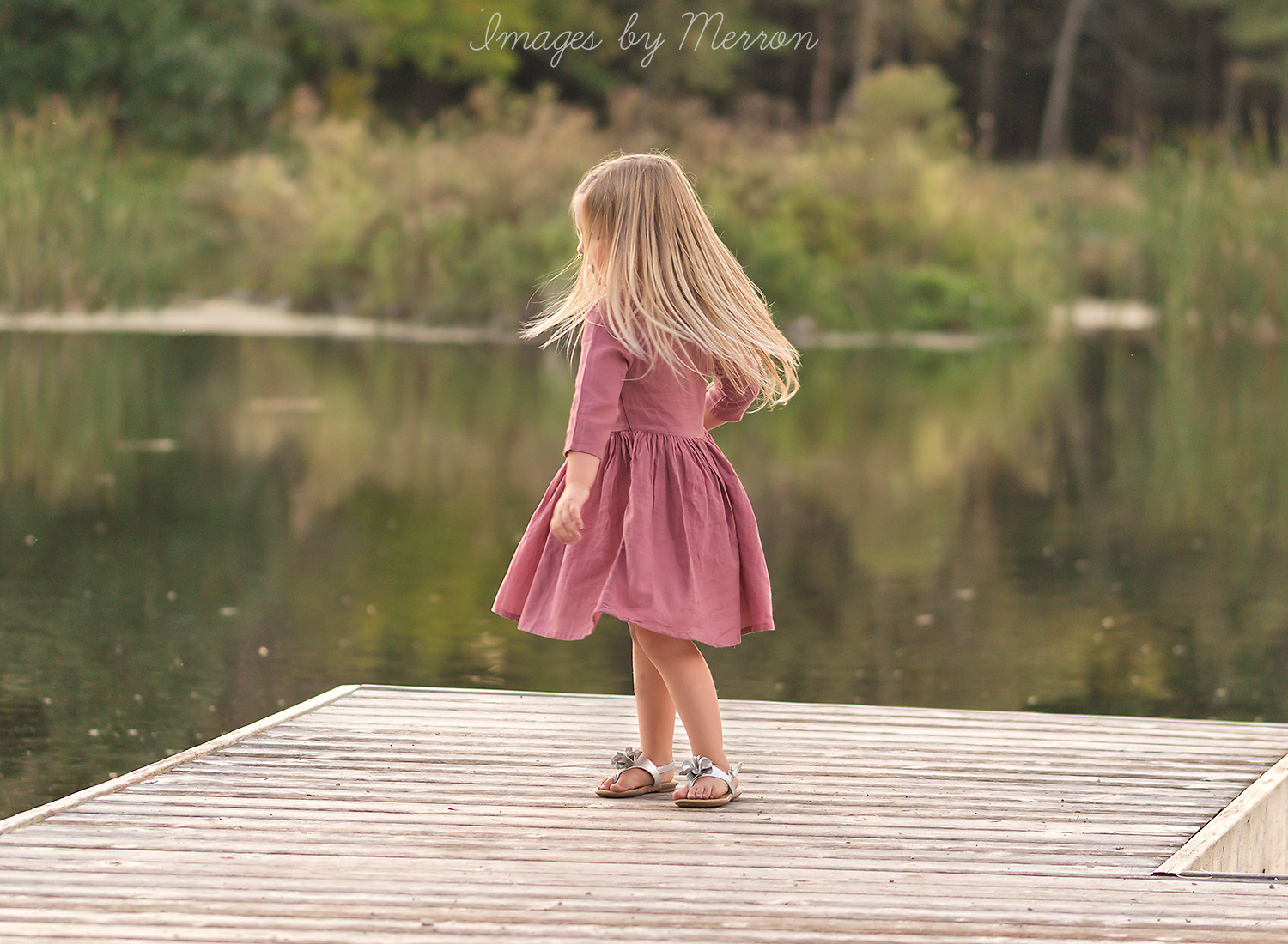 Girl twirling hair on dock at Jester Park in Iowa