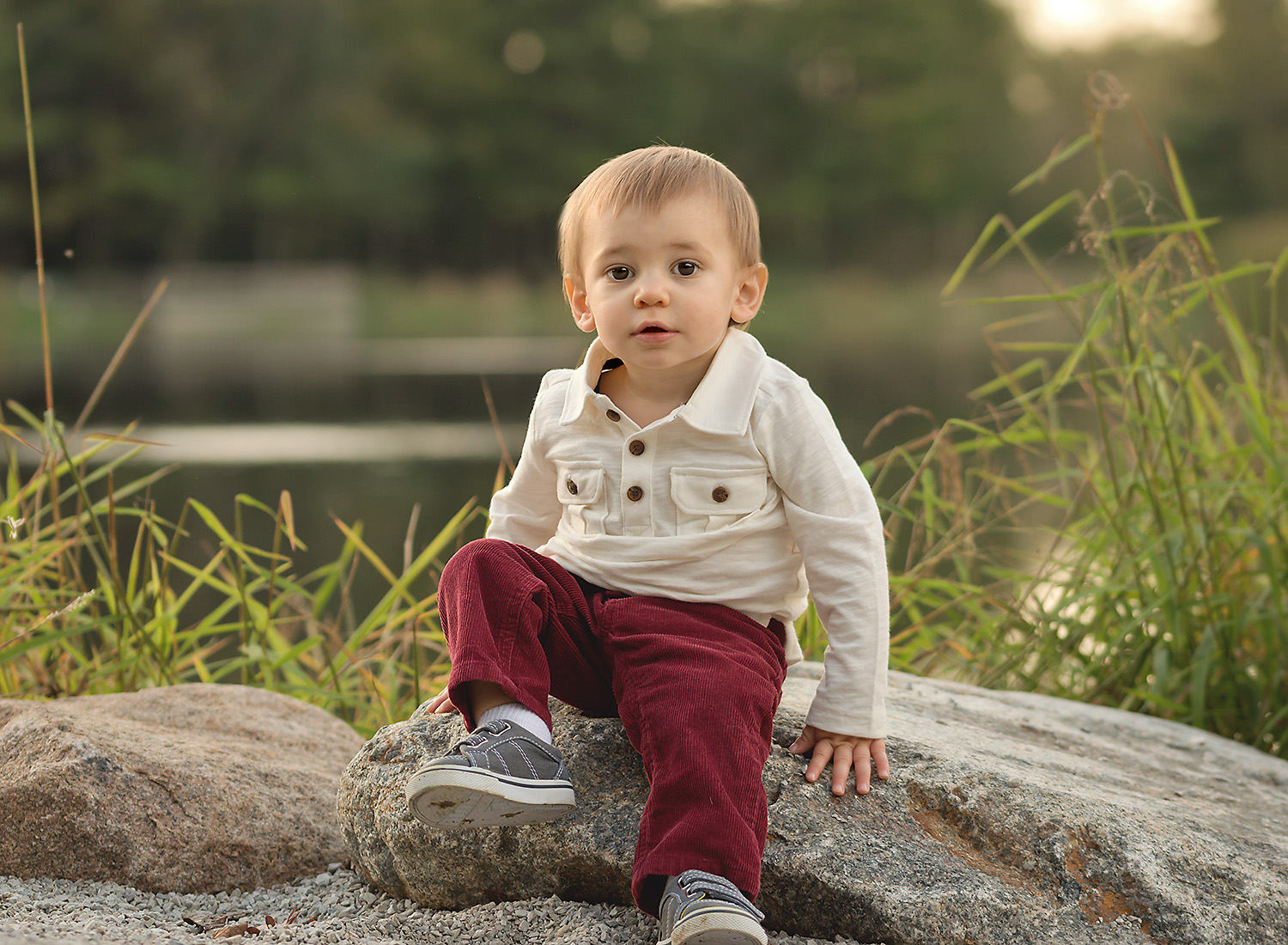 One year old boy sitting on rock during sunset at photography session