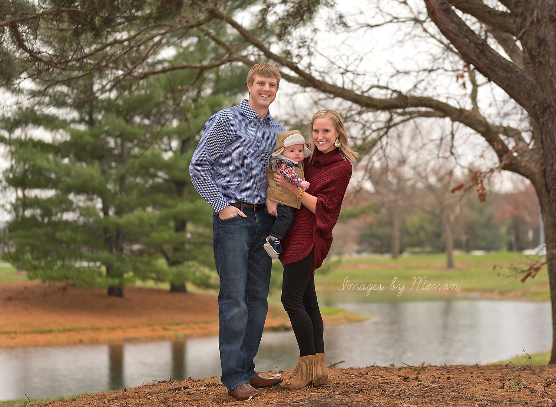 Family posing on rainy day, near pond