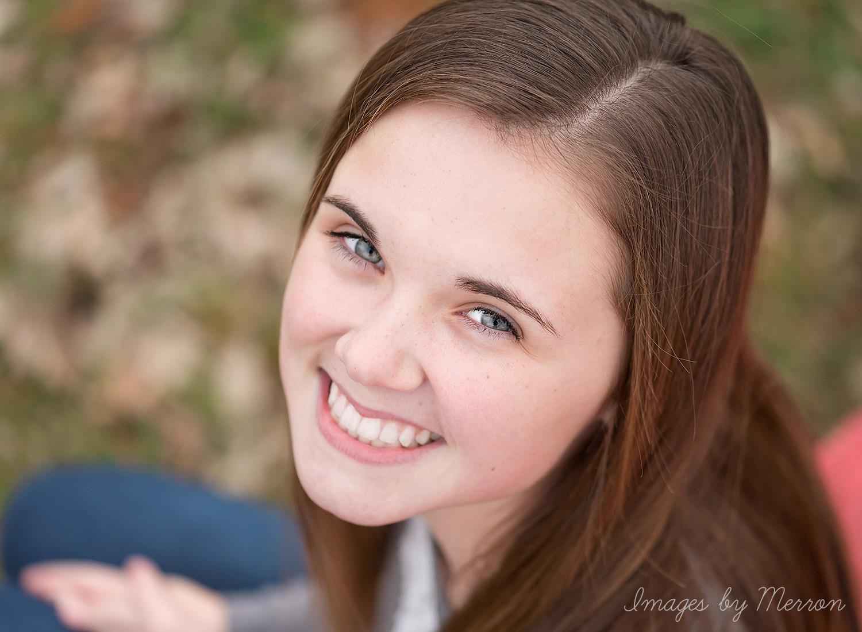 Teen girl looking up at camera, smiling