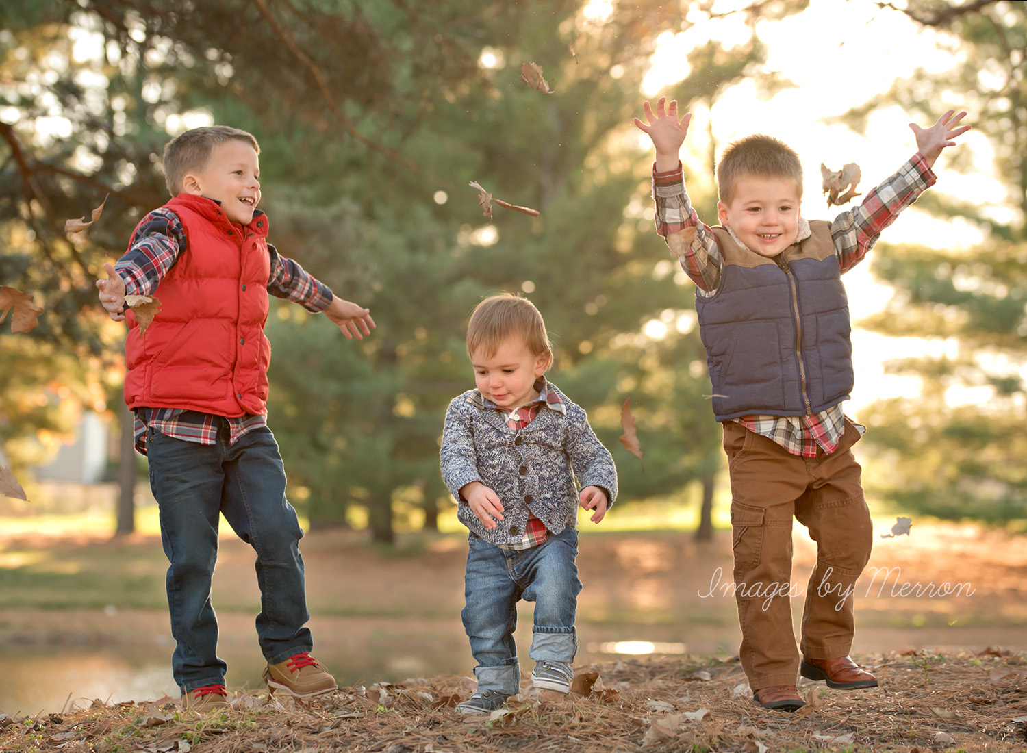 Children throwing leaves during photography session in Ankeny, Iowa