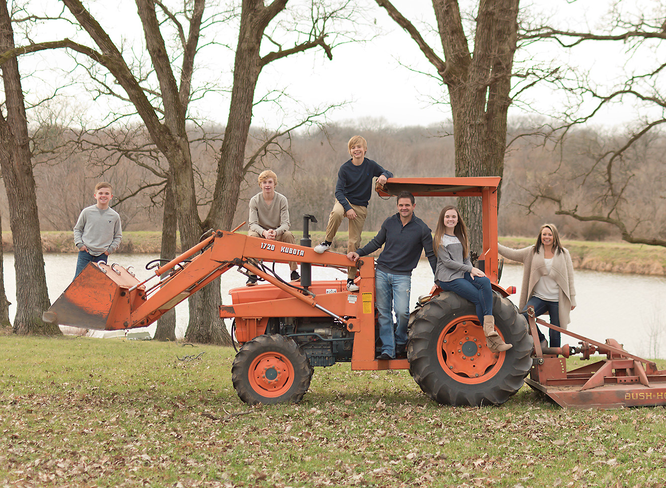 Large family posing on orange tractor in Iowa