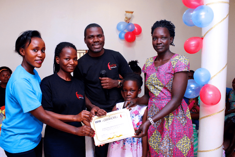 (Photo: Jesca receiving her certificate together with her daughter)