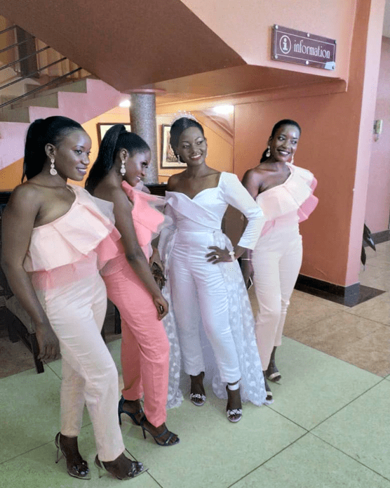 Catherine in her white jumpsuit posing for a photo with her bridal entourage.