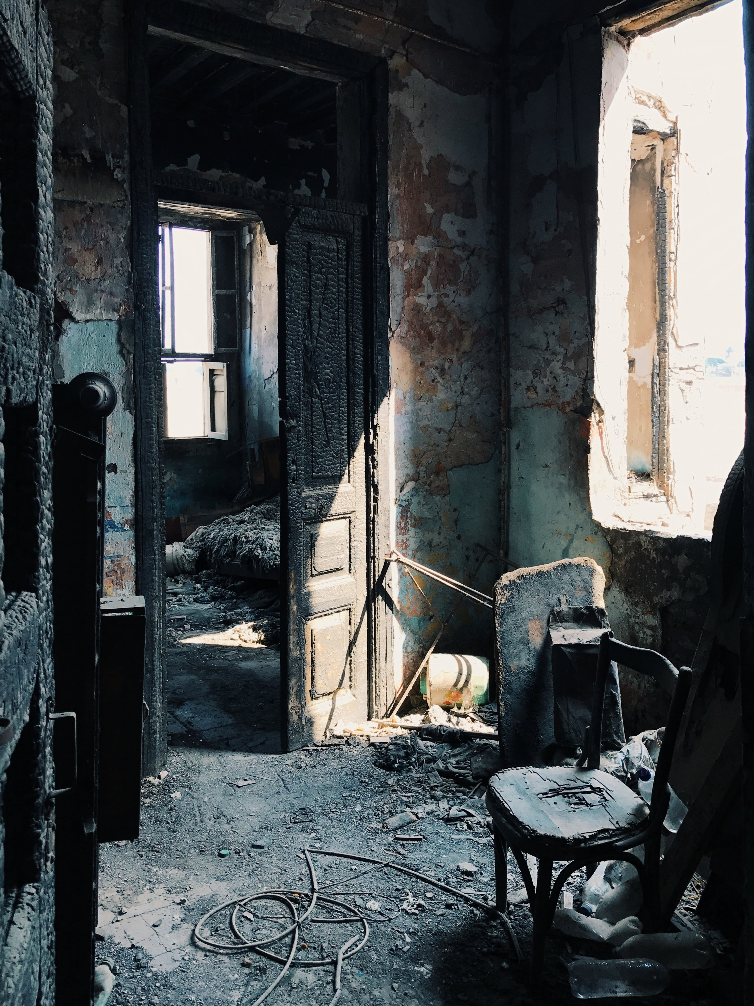 A burned door that remains shedding its ashes... its open leading to another room with a decayed bed that seems to have been beaten badly by the days...