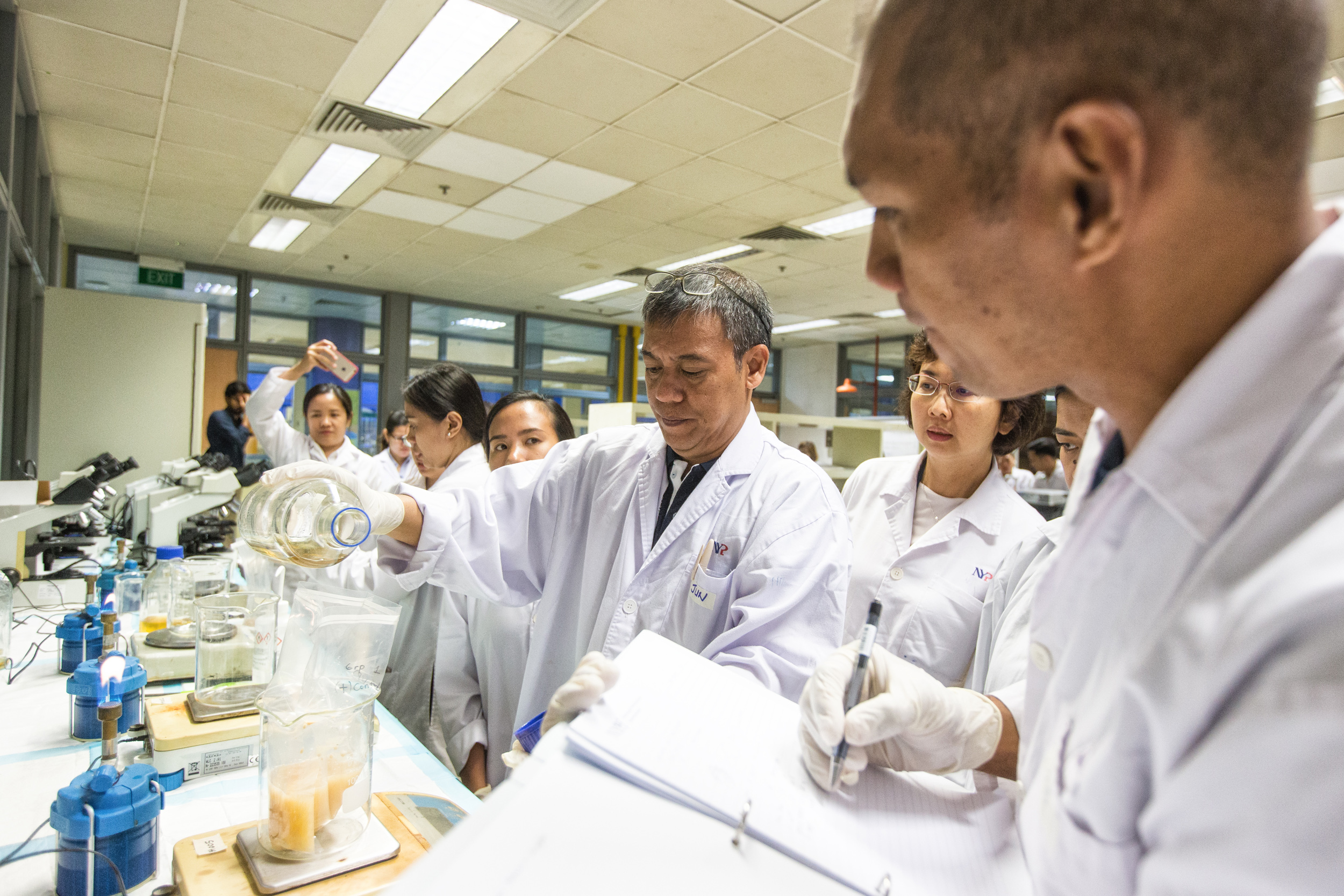 Jun Leo (centre) pours in the milk samples to its specific amount for microbiology testing. Other samples that are used for testing include salads and raw seafood-based foods.