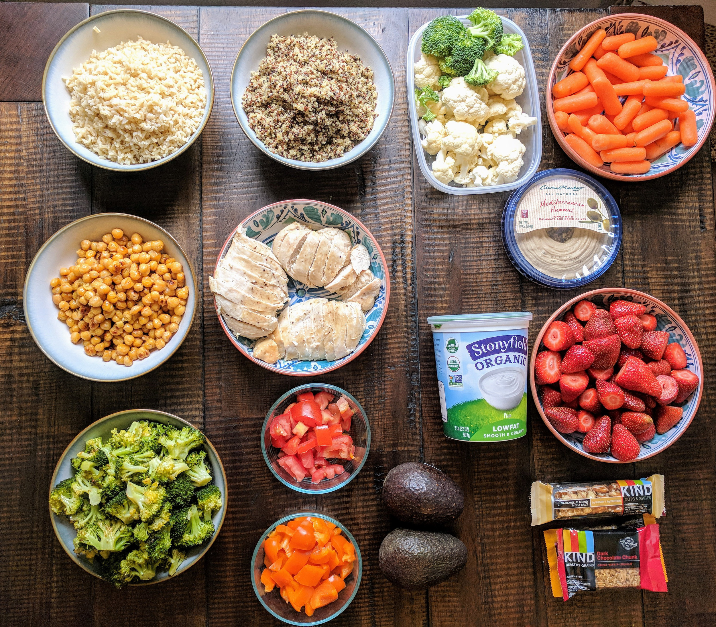 The final product of this meal preparation provides a variety of ingredients to build your own bowl including brown rice, quinoa, roasted chickpeas, grilled chicken, roasted broccoli, tomato, orange bell peppers, and avocados! Snacks are a breeze with hummus and pre - cut carrots, broccoli, and cauliflower. Breakfast are KIND bars and plain yogurt with strawberries for a sweet evening snack.