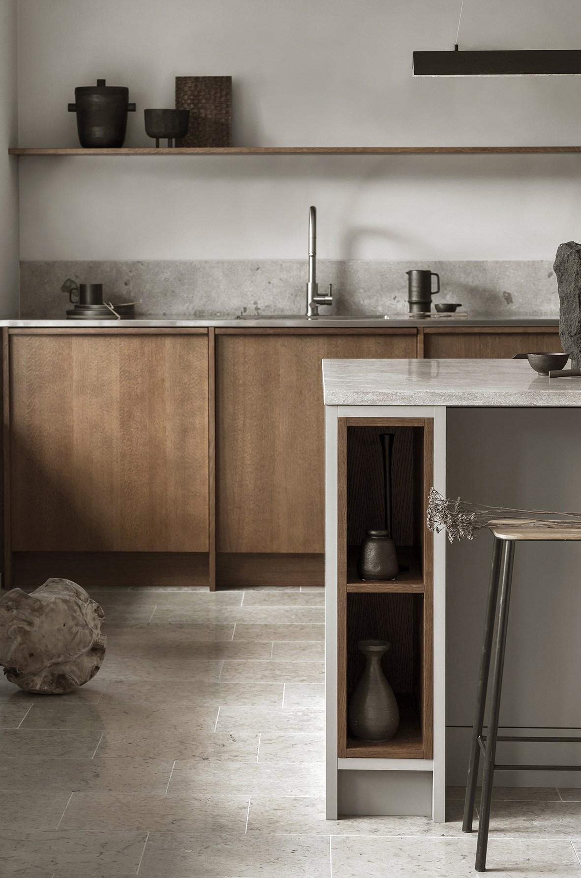 Kalkstensgolv, bänkskiva samt stänkskydd. Toppskiva i marmor på köksö. Referens från Nordiska kök