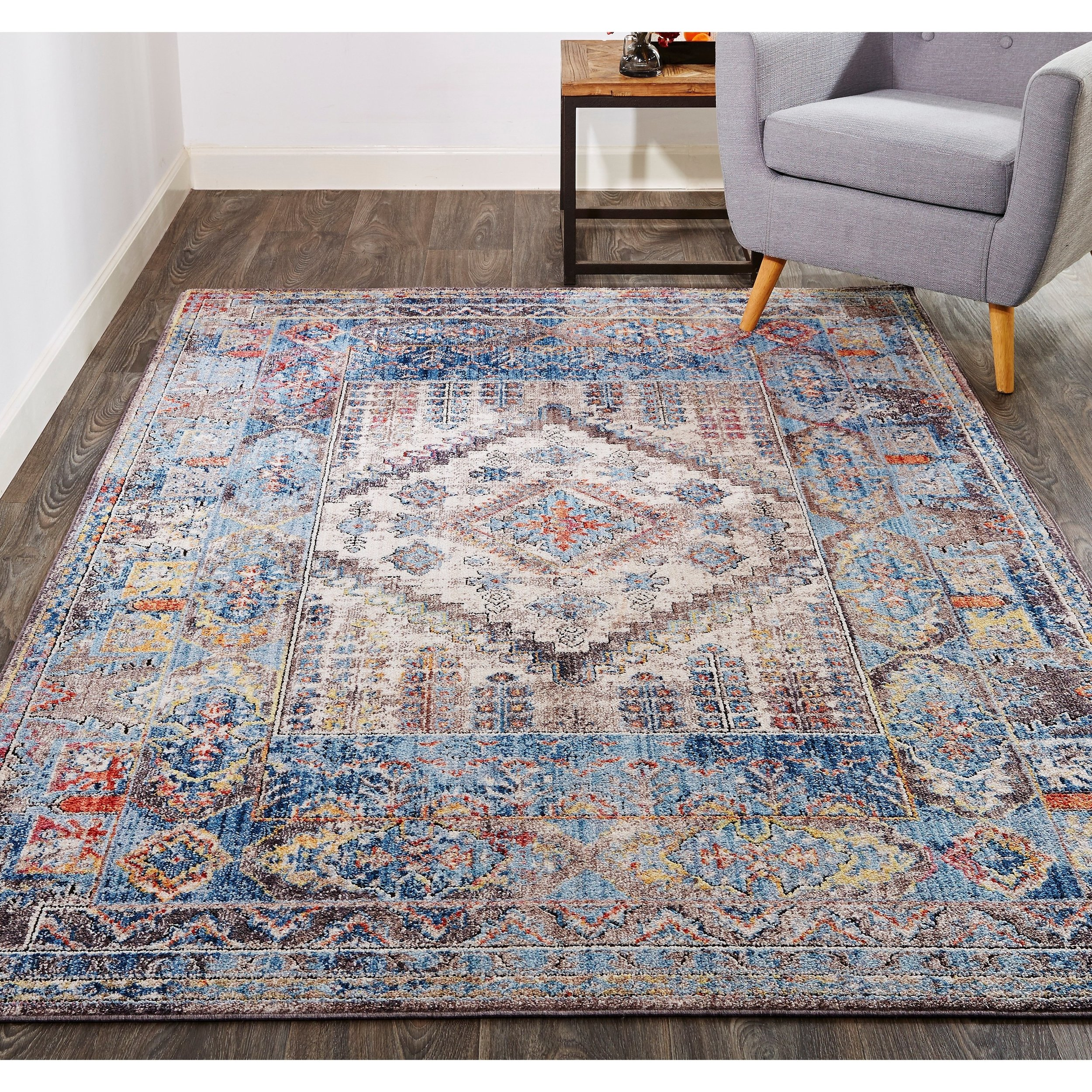 THE ARMANT RUG - A dazzling diamond medallion enlivens this traditional ornamental pattern as soothing cerulean and dramatic rust accent inviting ivory. The approachable color palette instantly transforms bohemian, eclectic, global and transitional spaces while the pure, stain-resistant polyester pile offers added durability for high traffic spaces.