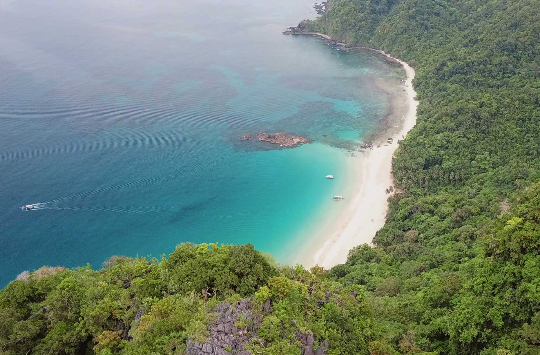 Aerial (drone) view of Cadlao Island's beautiful, soft sand beaches and clear turquoise waters.