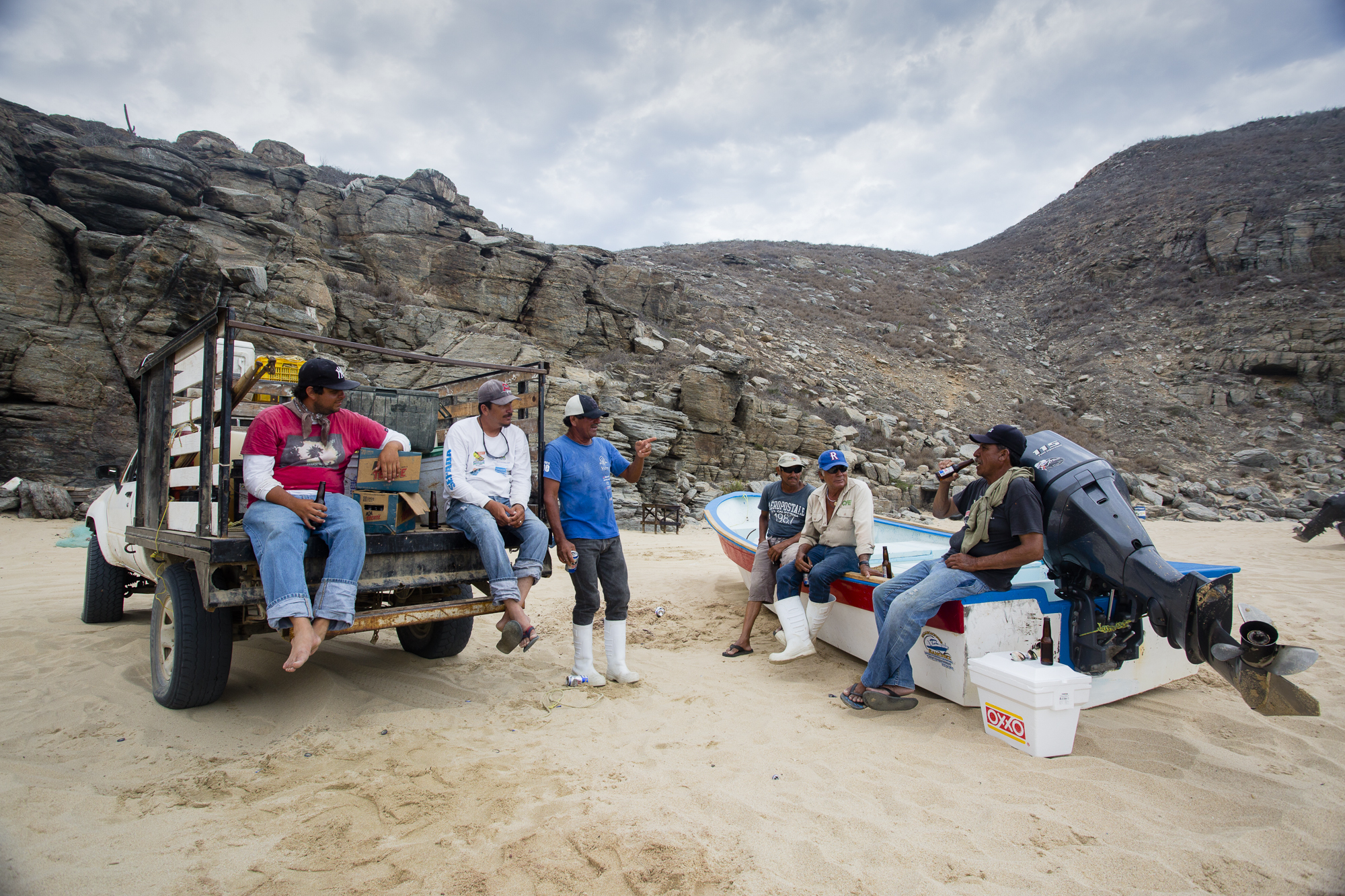 Fishermen chat and drink beer after finishing a work day. The fishermen of Punta Lobos have formed a tightly-knit community; many of them have been working together for years, and many come from families that have been working in Punta Lobos for generations.
