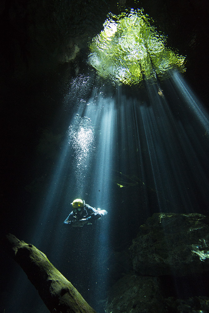 Cave diver Manuel Allende swims through rays of sunlight at cenote Sugar Bowl, part of the Tajma Ha cave system, in the Riviera Maya, Mexico.