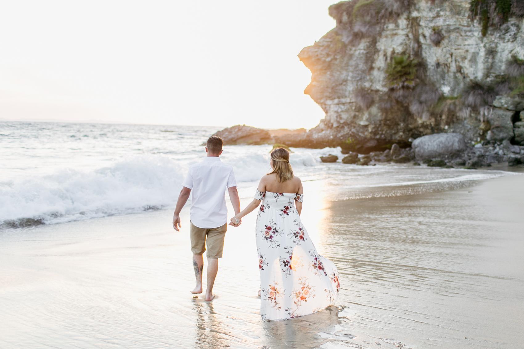 Couple walking towards ocean during maternity session at Thousand Steps Beach with Laguna Beach maternity photographer Lovisa Photo.
