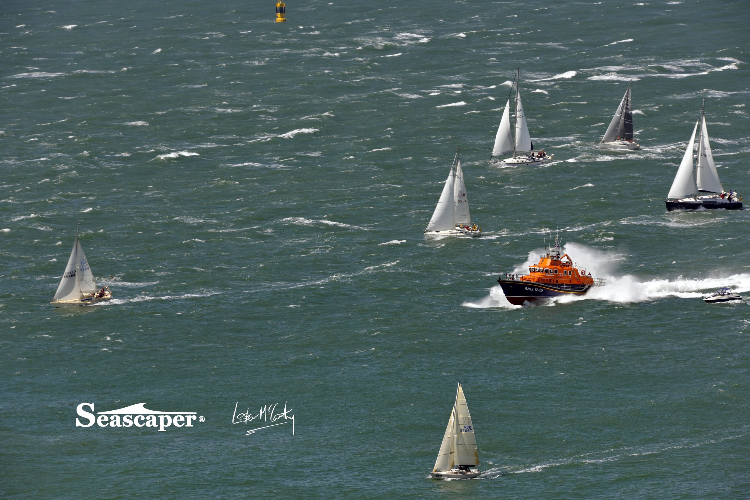 The RNLI Yarmouth lifeboat speeds through the fleet to get to the stricken vessel.