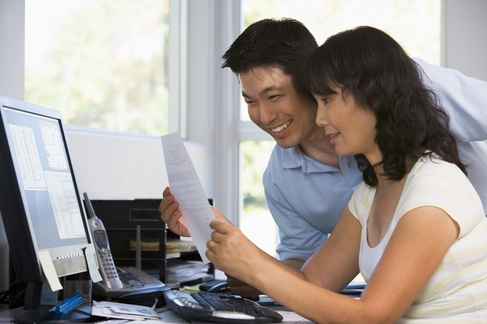 couple-in-home-office-with-computer-and-paperwork-smiling_rFOjoPCBi.png