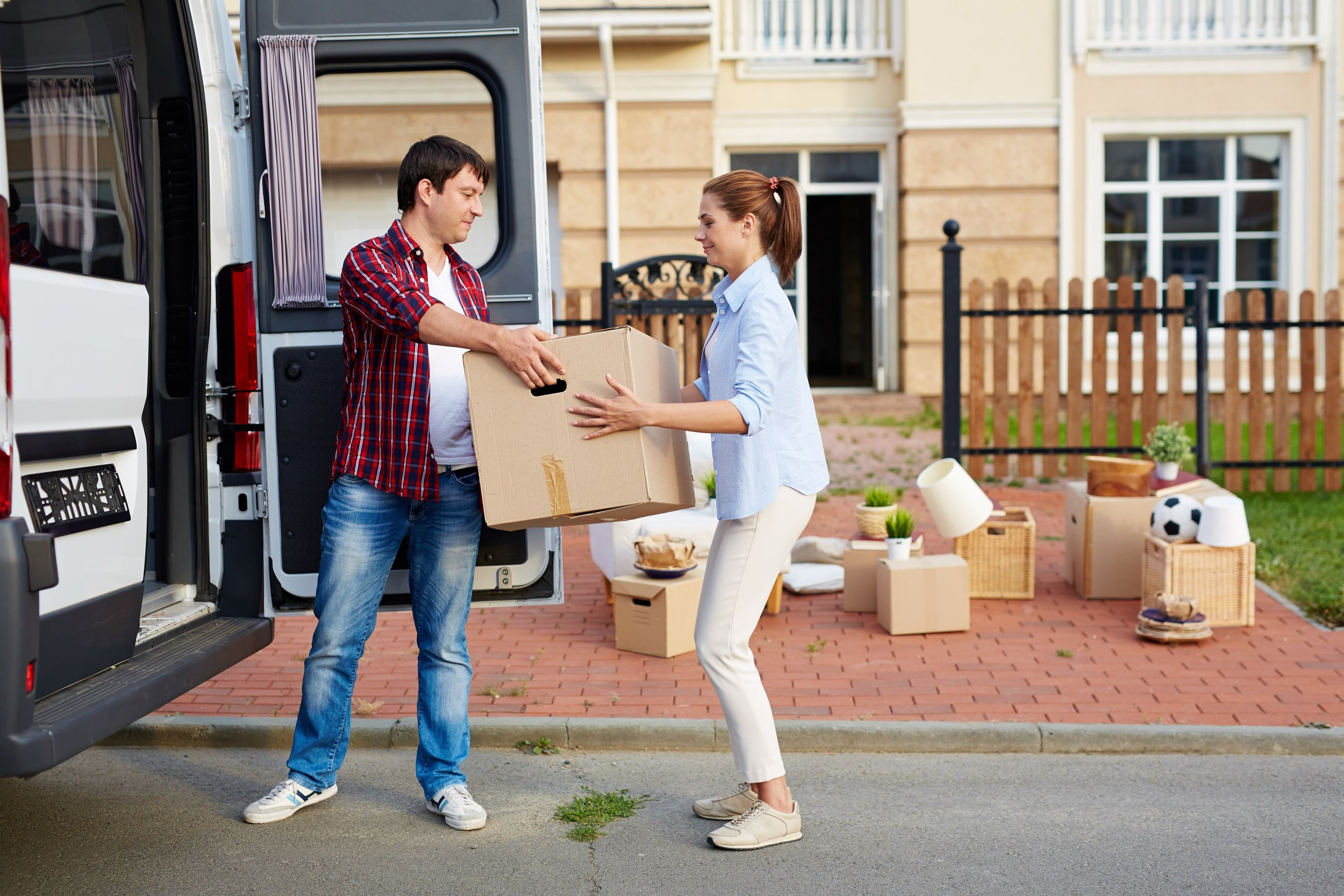 storyblocks-portrait-of-man-taking-cardboard-boxes-out-of-moving-van-and-passing-them-to-his-wife-in-front-of-new-house_B3-7ourJkz-sm.jpg