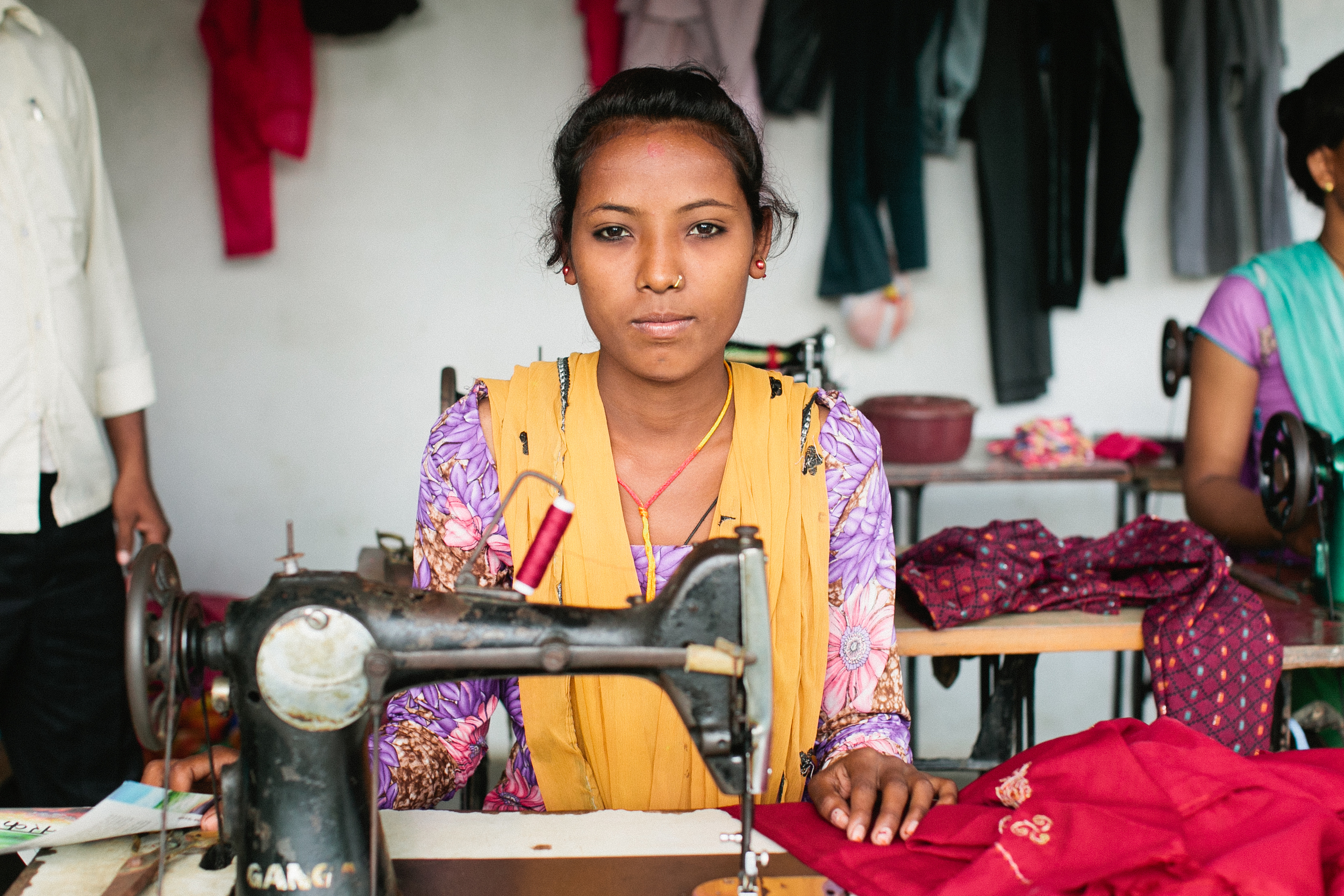 A village woman is able to use a sewing machine to make and sell items to help support her family.