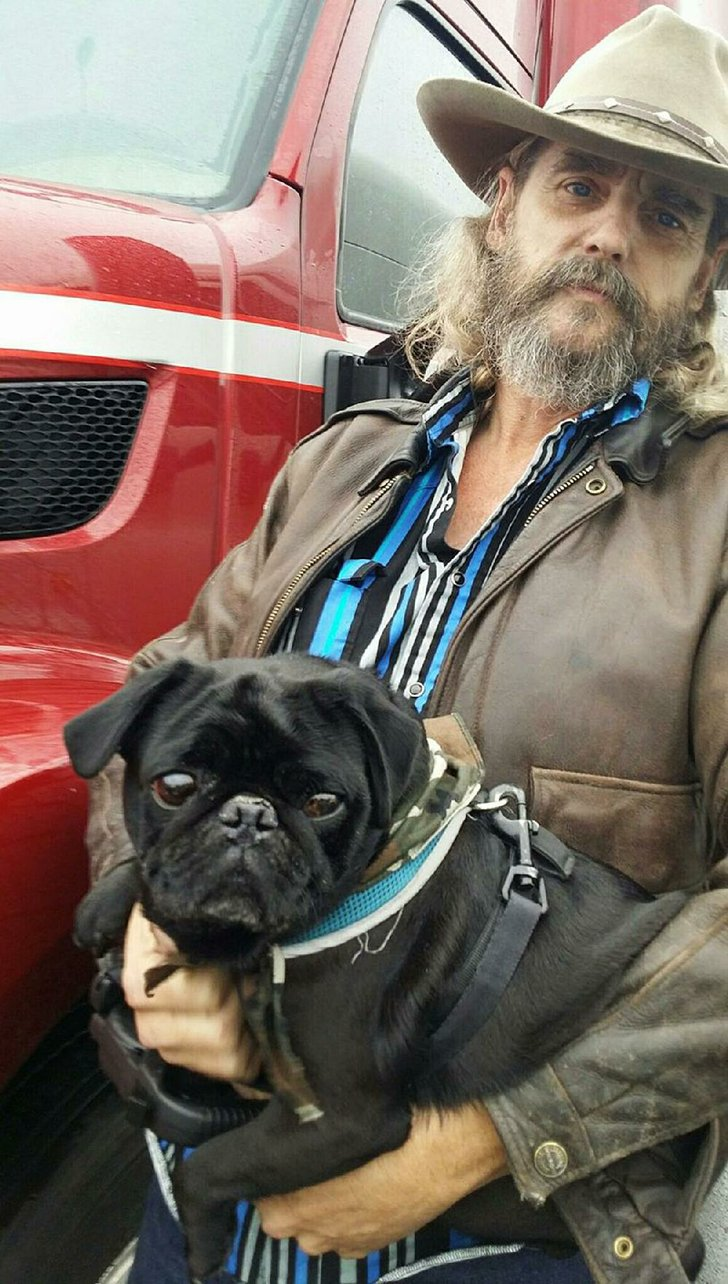Truck driver Jim Farmer holds Bruiser. Farmer is part of Operation Roger, a nonprofit that matches truck drivers with rescued pets for transport across the country.