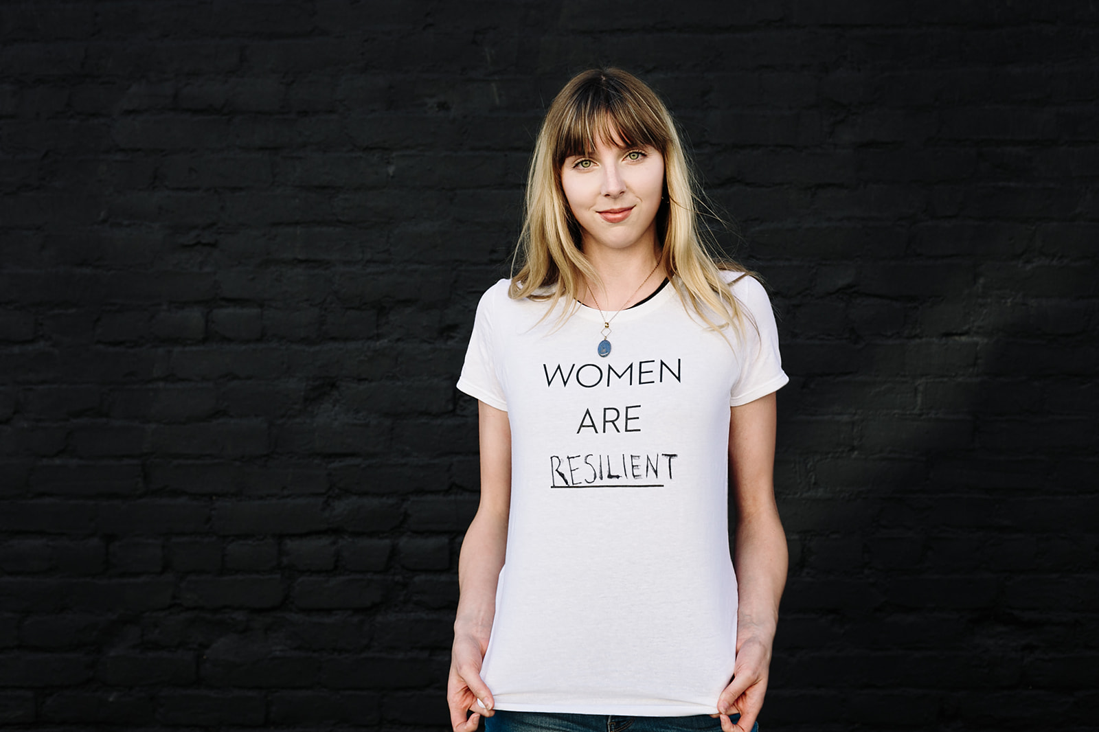 "Brighid Quinn wearing her ""Women are Resilient"" t-shirt inspired by one of our Instagram followers! Thank you @raejus!  Photo by  Even Keel Imagery  -  Miriam Brummel ."