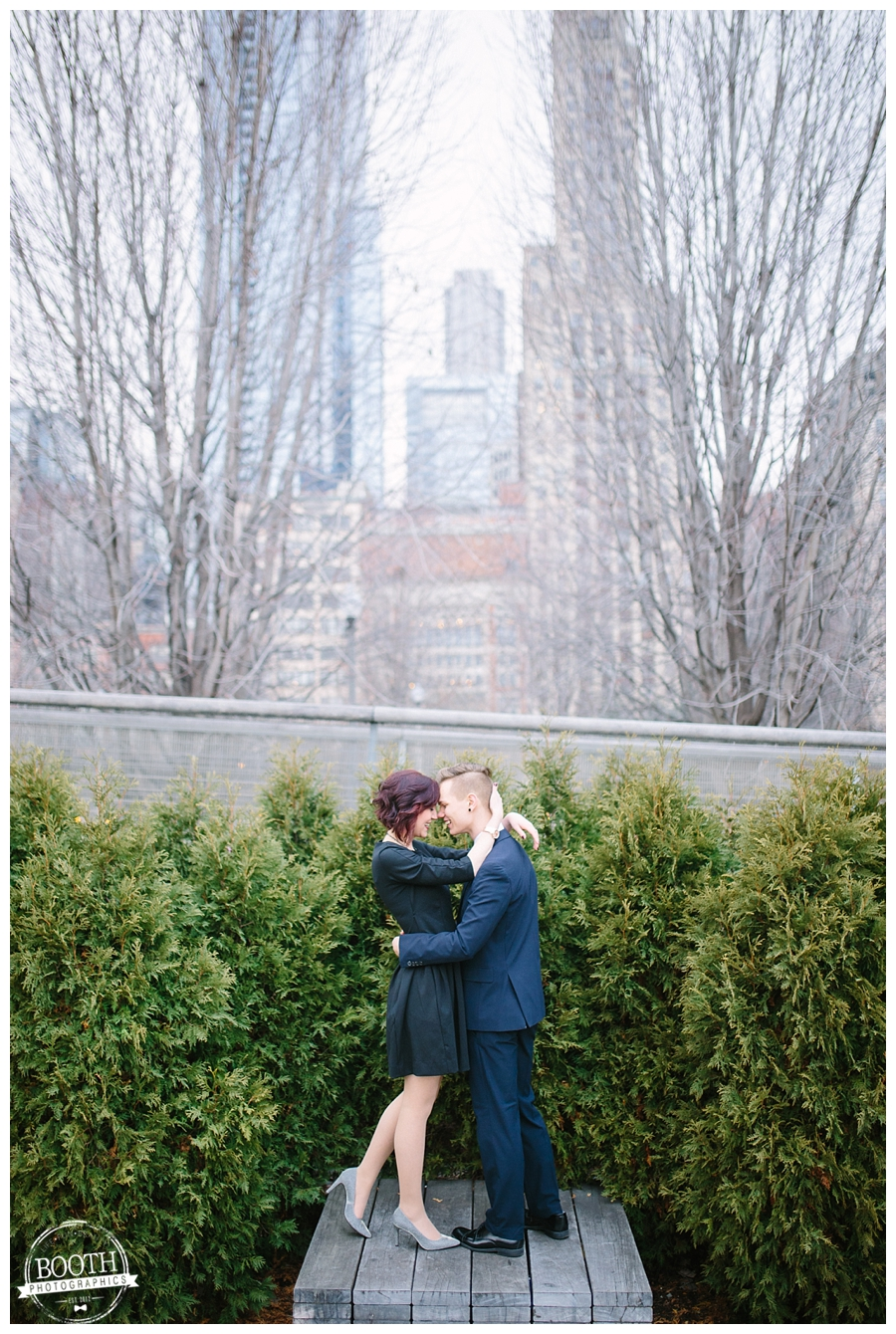 engaged couple standing on a bench and kissing in Millenium Park in downtown Chicago, IL