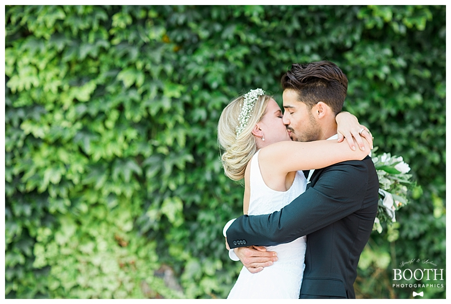 couple kissing in front of ivy covered wall at their romantic, industrial wedding at the Pritzlaff Events