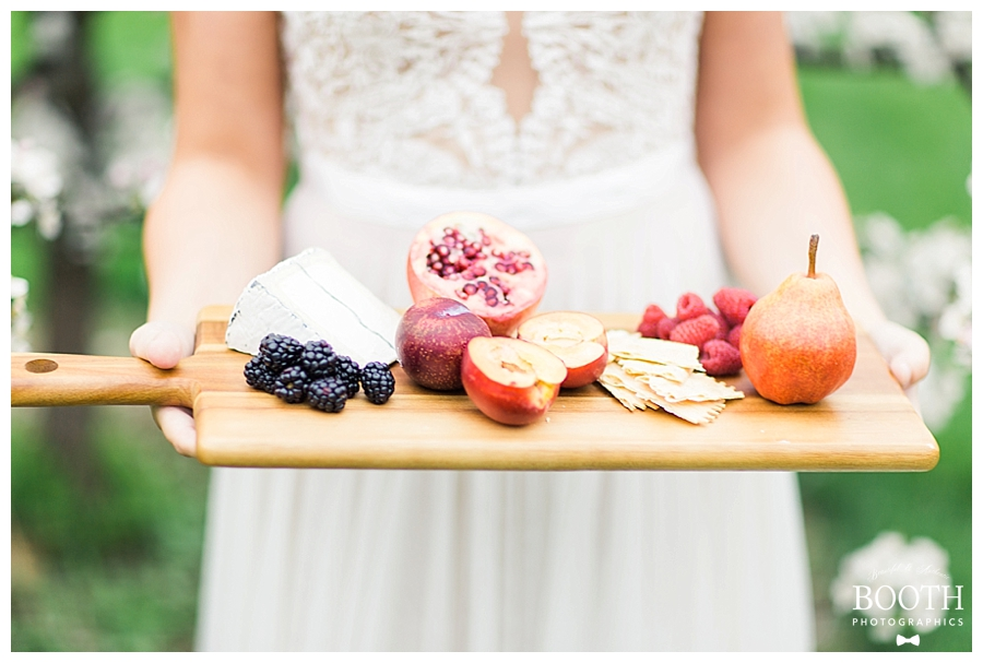 bride wearing BHLDN gown and holding rustic cheese and fruit platter