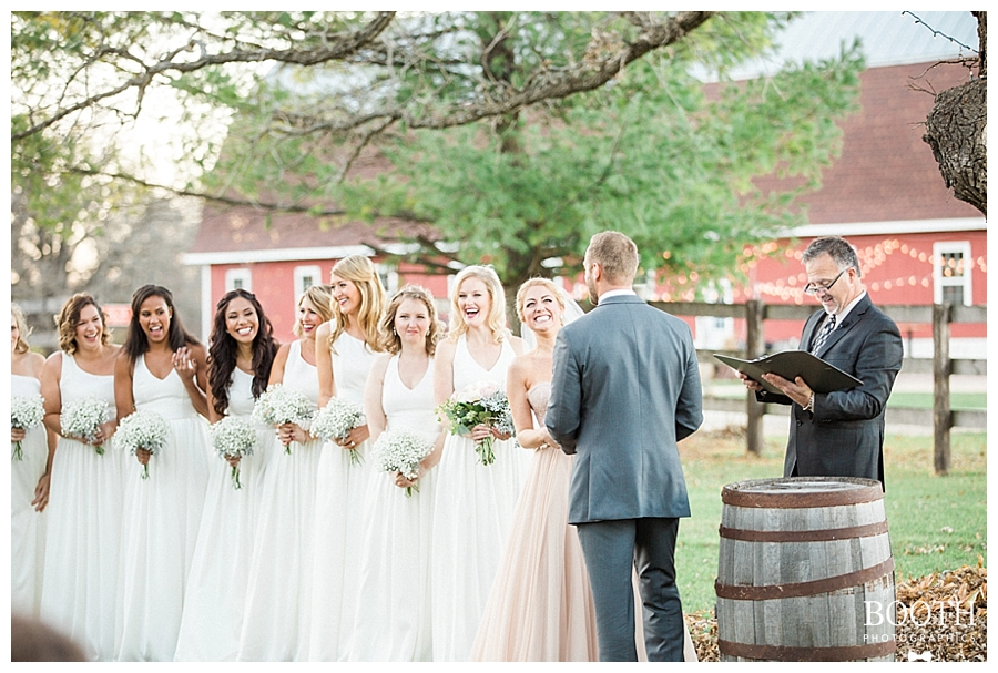 bride wearing blush and bridesmaids wearing white while bride and groom exchange vows at their rustic glam outdoor wedding