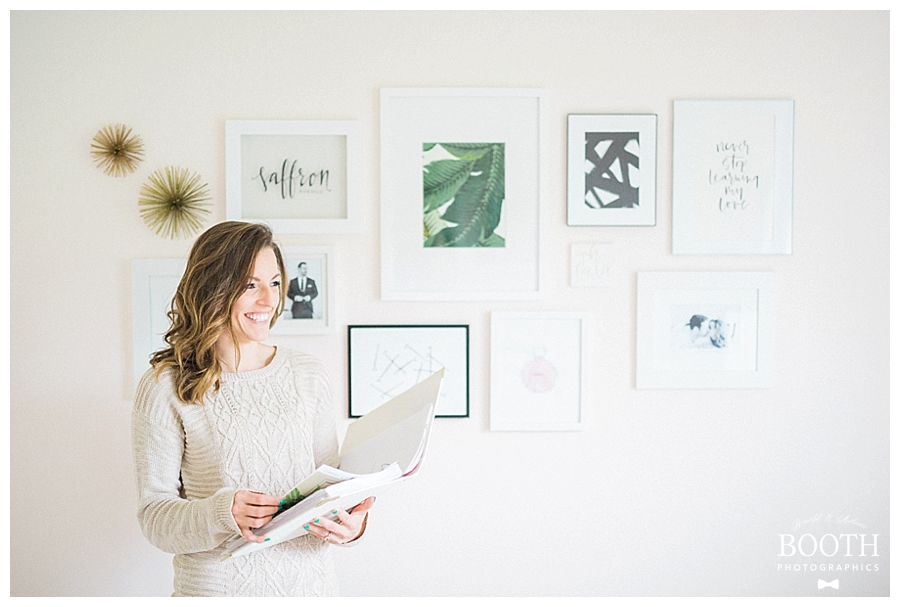 Style Me Pretty blogger bride smiling and holding her Southern Weddings planner in front of mid century modern inspired gallery wall