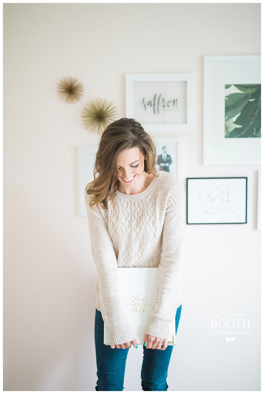 bride smiling and holding her Southern Weddings planner in front of mid century modern inspired gallery wall