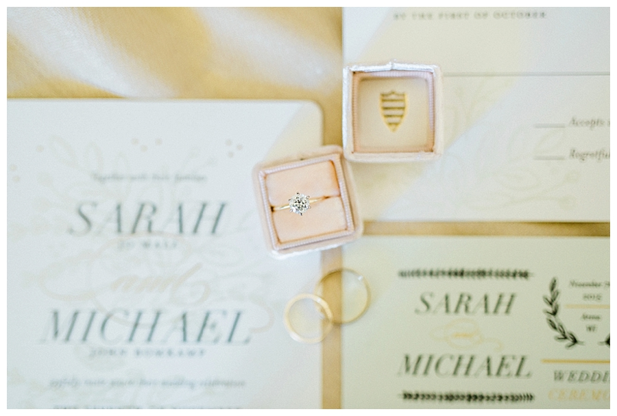 wedding ring in a blush The Mrs. Box atop wedding stationary at a rustic outdoor fall wedding