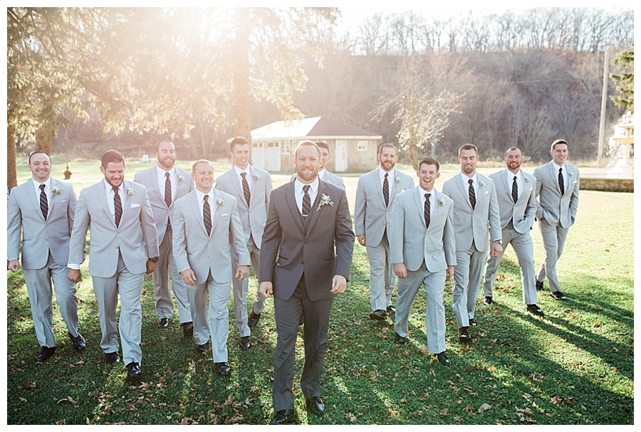 groom walking with his groomsment for his rustic fall outdoor wedding