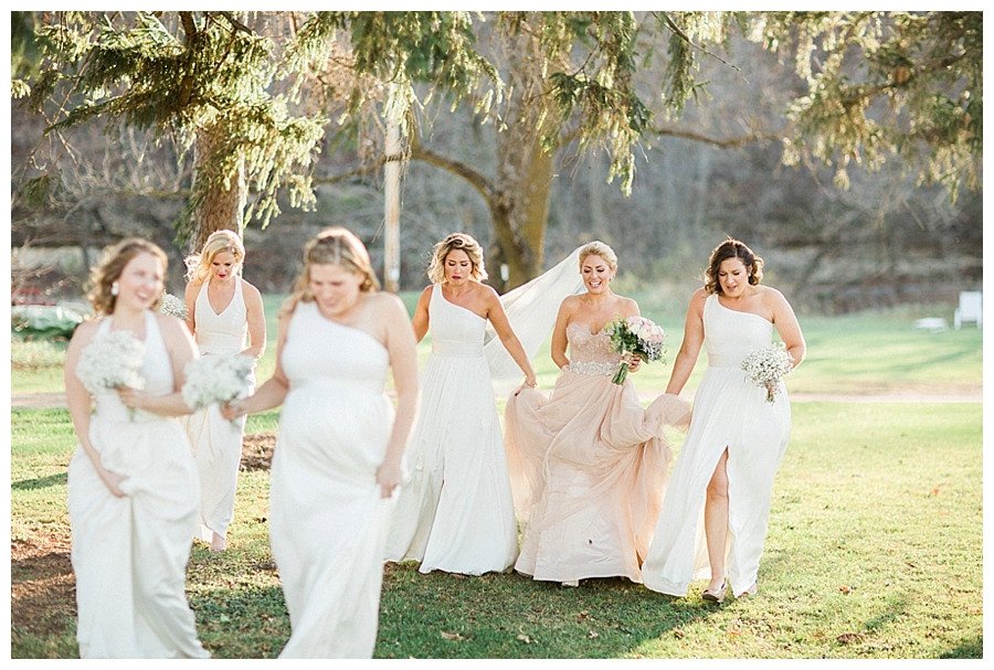 Bride walking with her bridesmaids at her rustic fall outdoor wedding