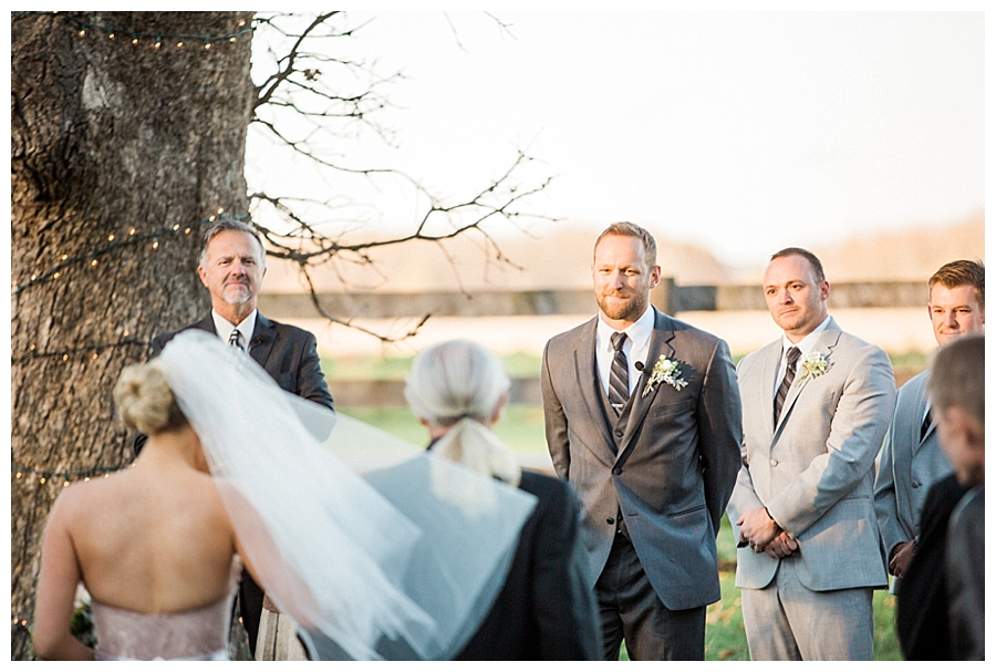 Groom grinning at his bride as she walks the aisle for their rustic outdoor wedding ceremony at Sugarland Barn
