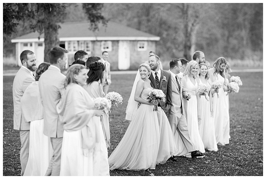 bride and groom walking with their bridal party at their rustic outdoor wedding at Sugarland Barn