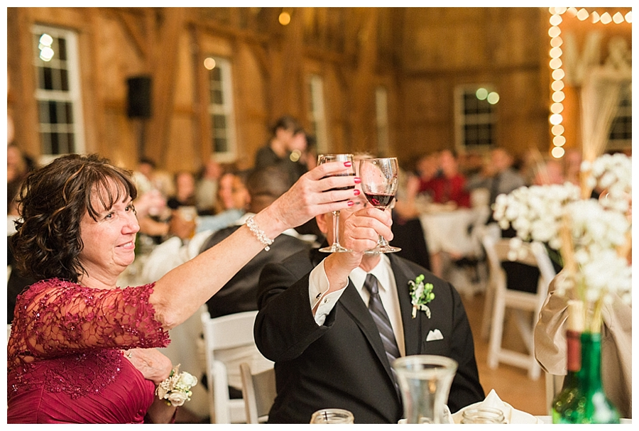 guests toasting the bride and groom at a rustic fall wedding reception at Sugarland Barn